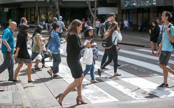 on smartphone crossing the street